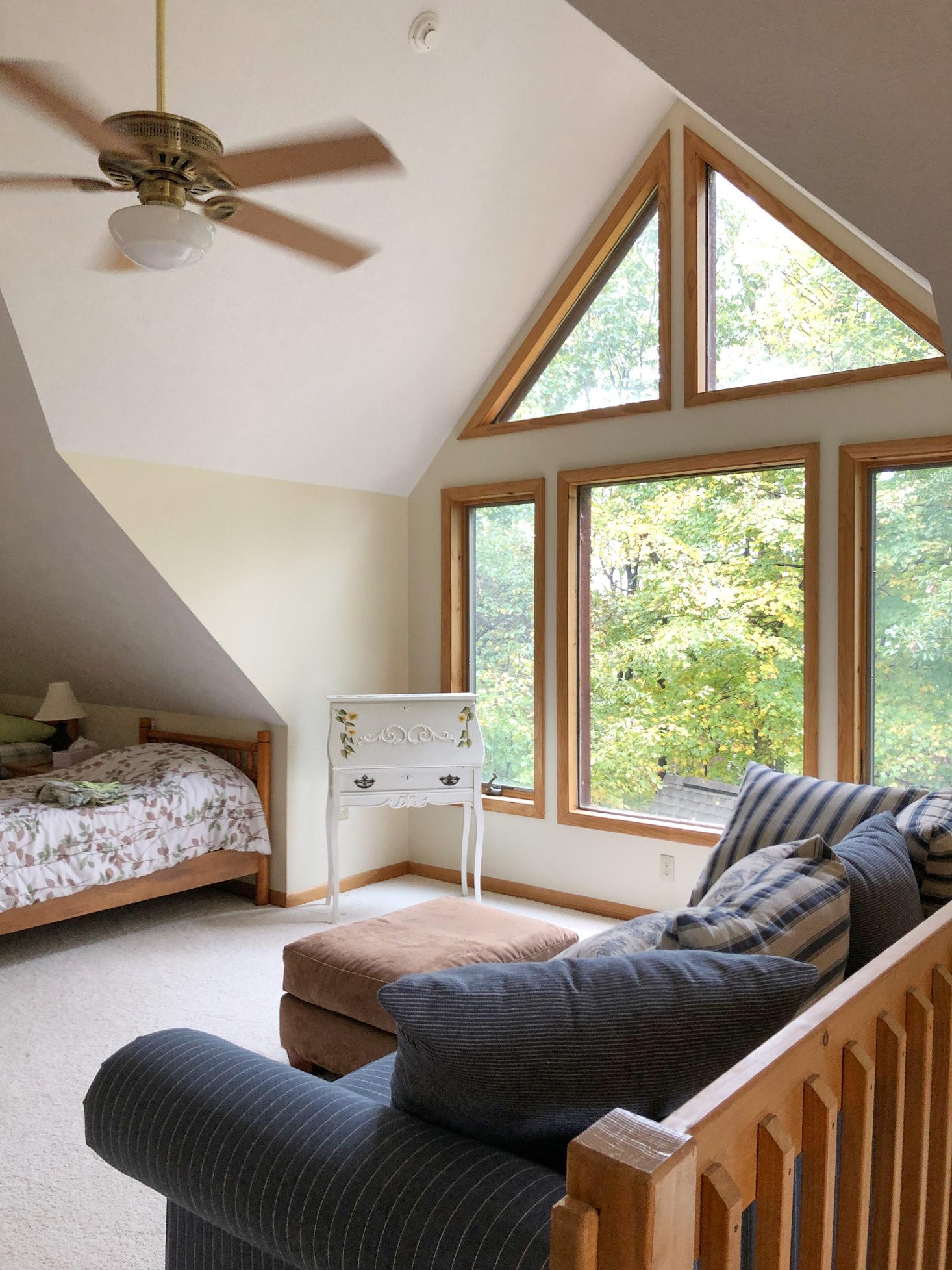 Triangle windows and ceiling fan in cabin loft