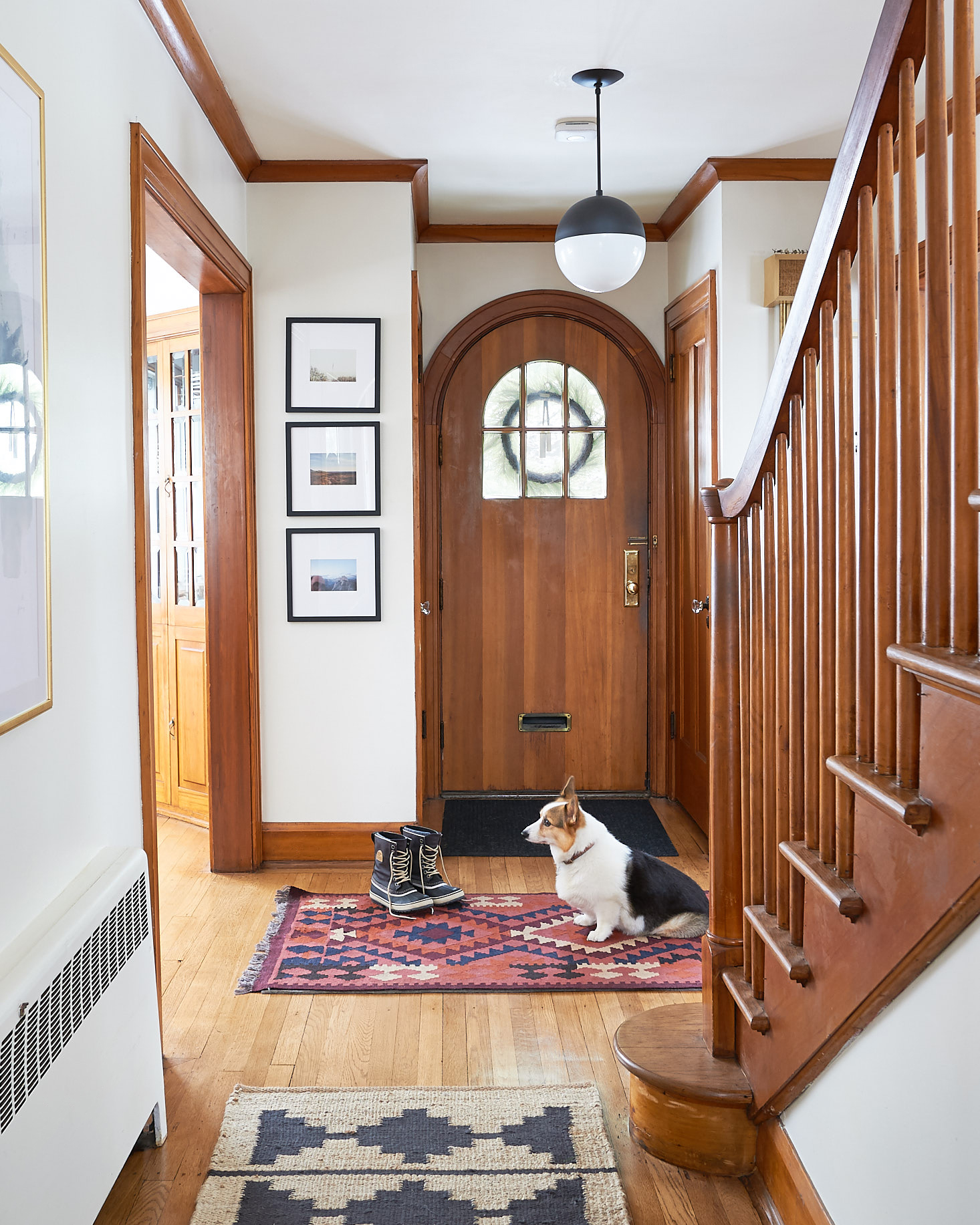 Round front door with stacked art and a wooden staircase