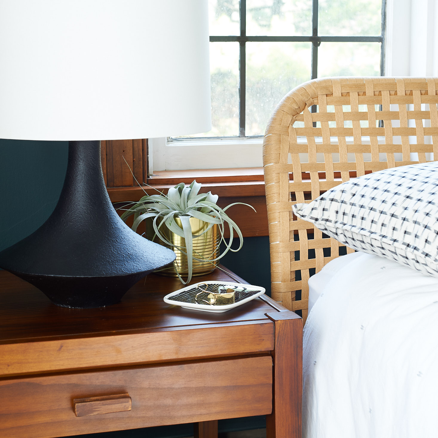 Nightstand with midcentury lamp and rattan headboard
