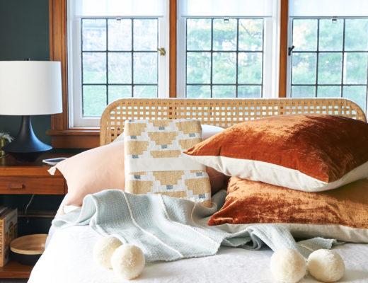 Pom pom throw, rust velvet pillows, linen duvet in a pile.