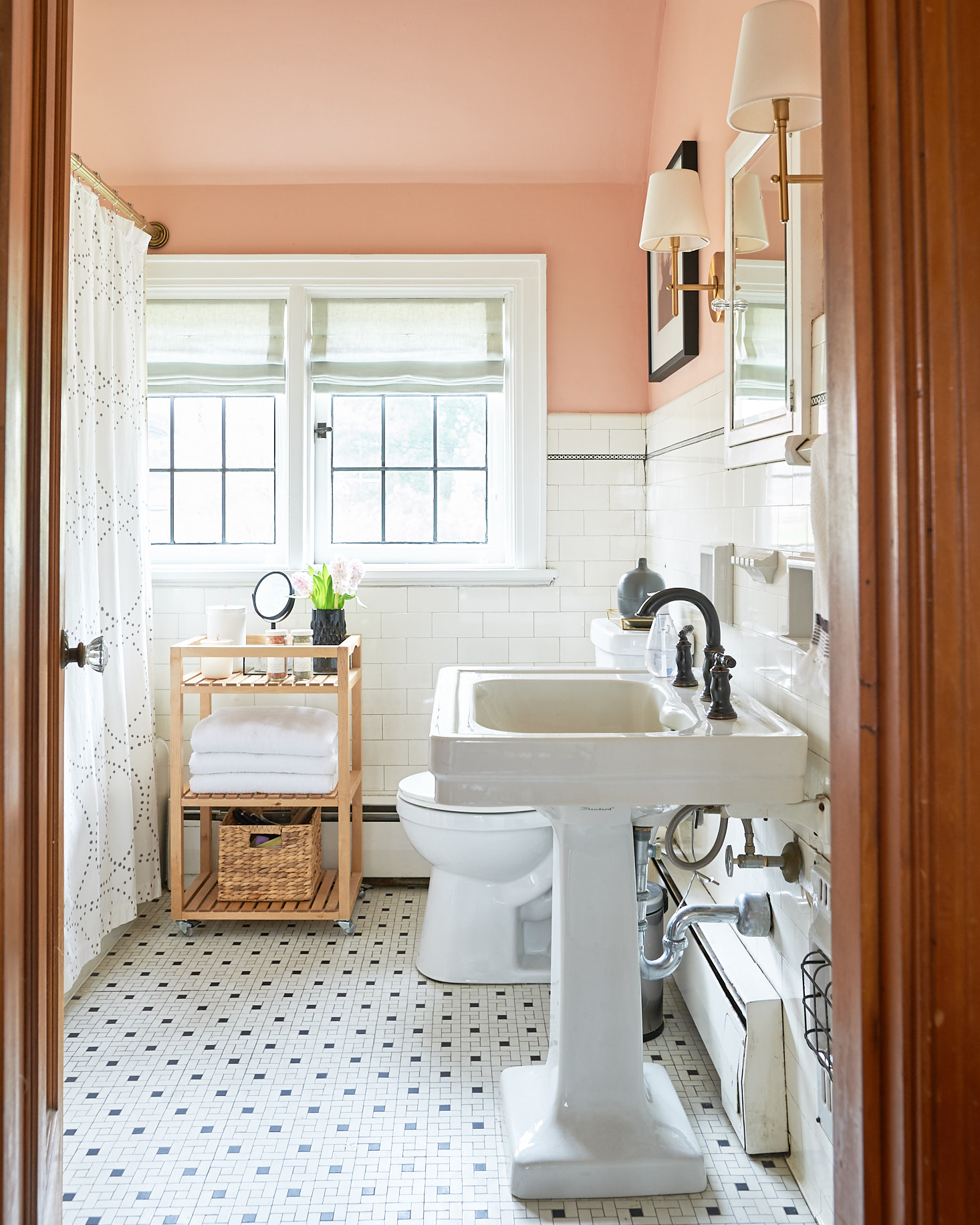 Blush bathroom with linen roman shades and classic tile