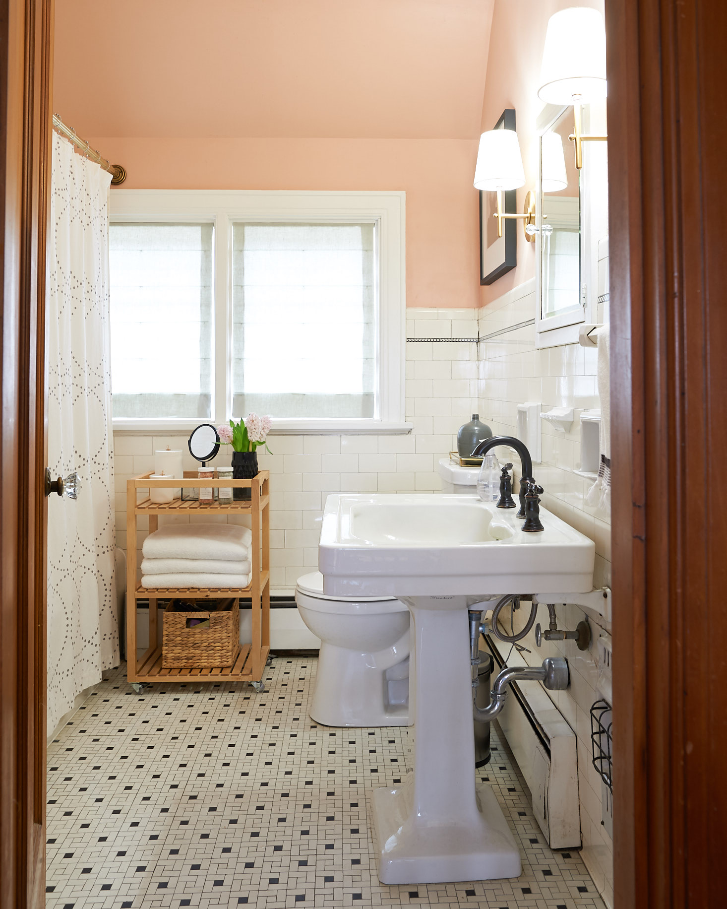 Blush bathroom with shades drawn lit by sconces