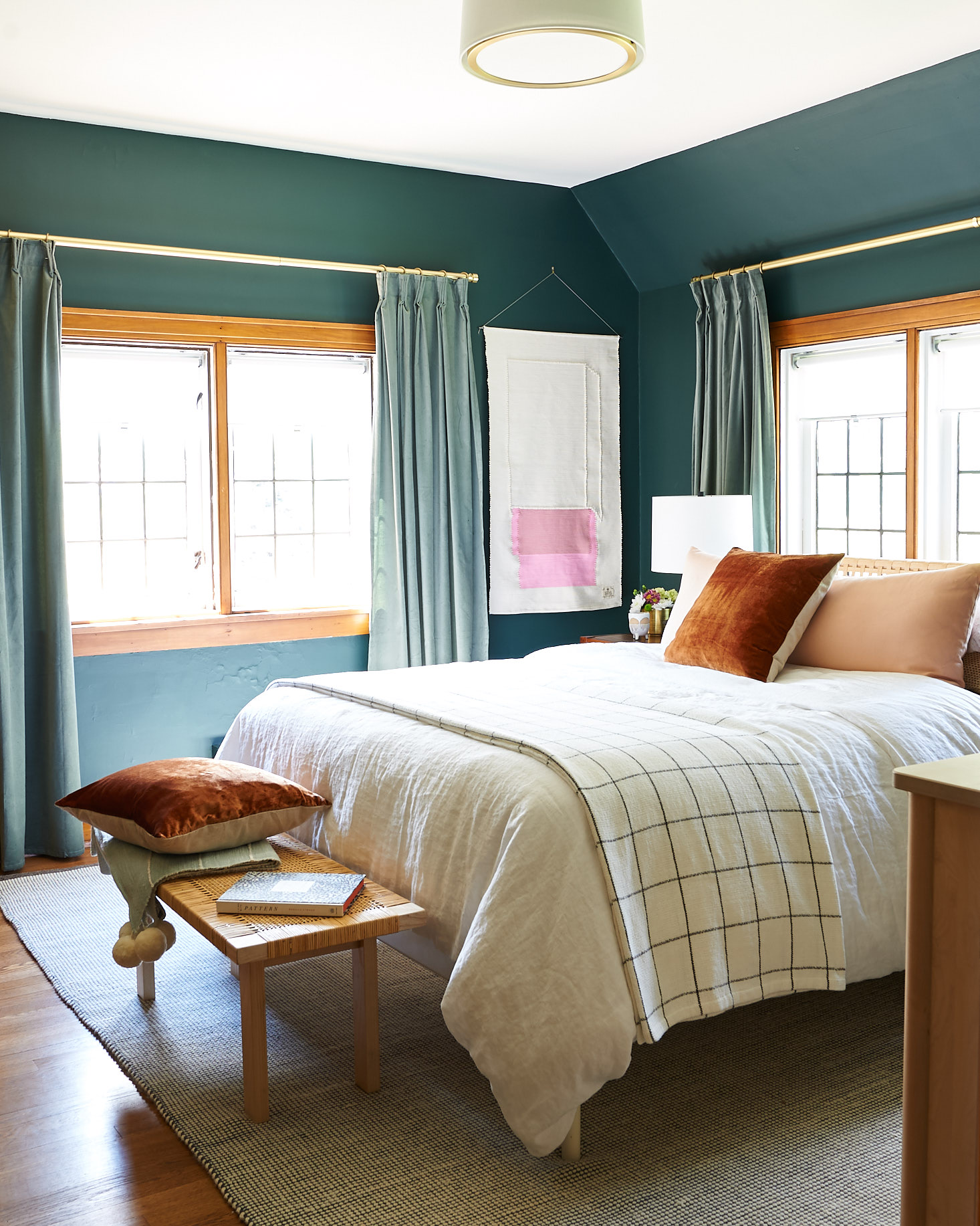Green guest room with bright bedding