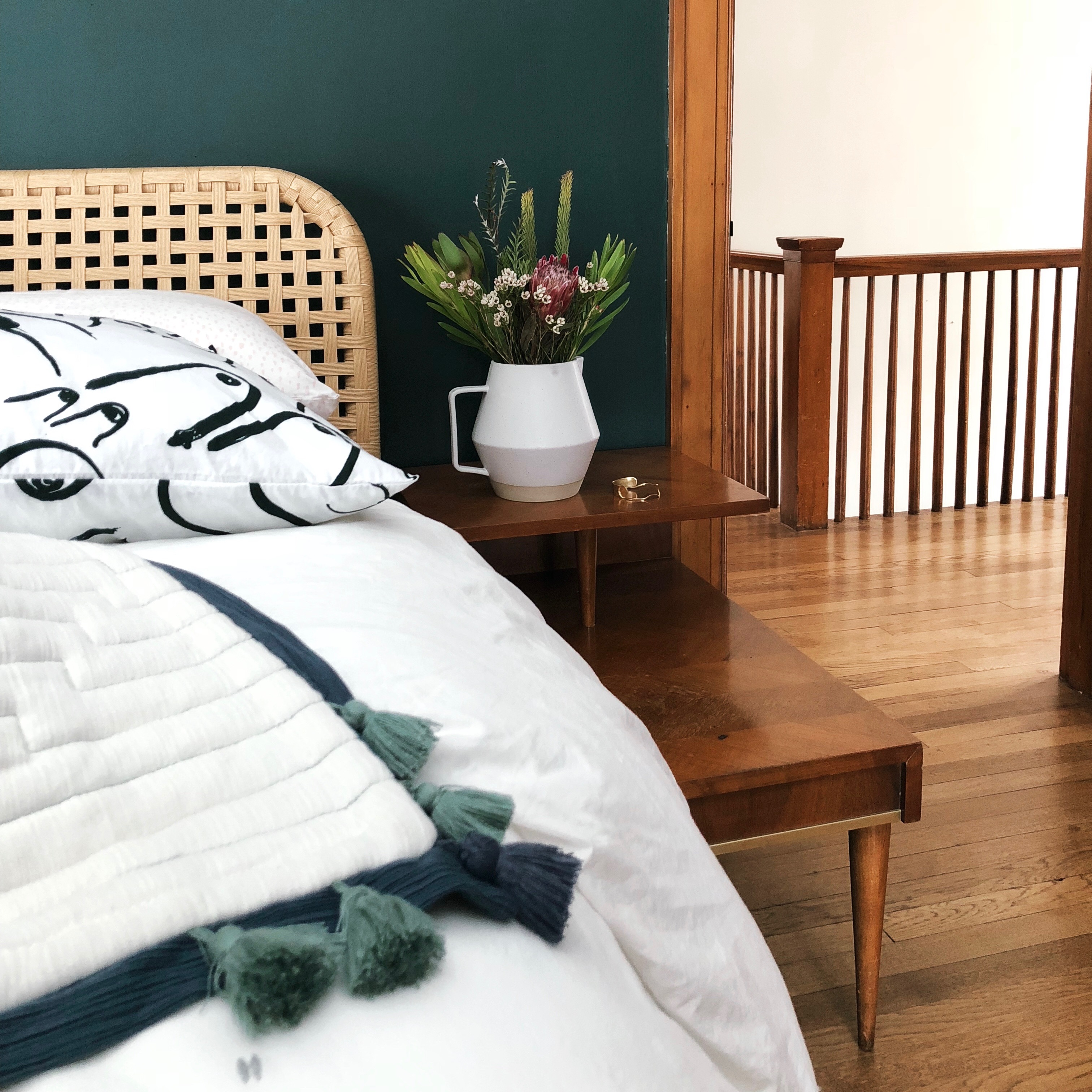 Green Guest Bedroom with Vase and Tassel Quilt